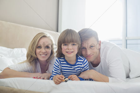 Love : Portrait of happy parents lying with son in bed