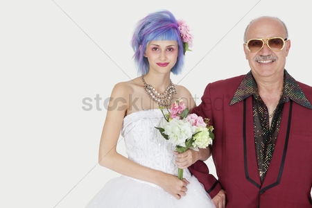 Man suit fashion : Portrait of happy senior man standing arm in arm with beautiful daughter in wedding dress against gray background