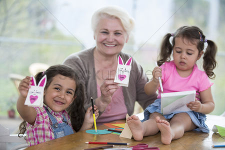 Czech republic : Portrait of happy senior woman showing craft rabbit while sitting with granddaughters at home