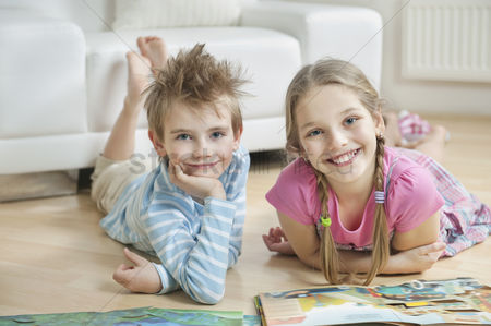 Czech republic : Portrait of happy siblings with story books lying on floor in living room