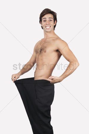 Loss : Portrait of happy young man wearing oversized pants against gray background