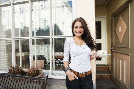 Smiling : Portrait of happy young woman holding coffee cup in front of cafe