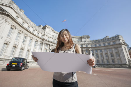 England : Portrait of happy young woman holding map against admiralty arch in london  england  uk