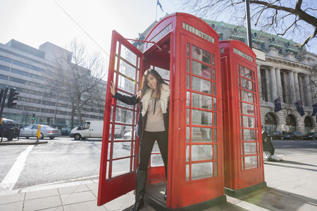 England : Portrait of happy young woman opening door of telephone booth at london  england  uk
