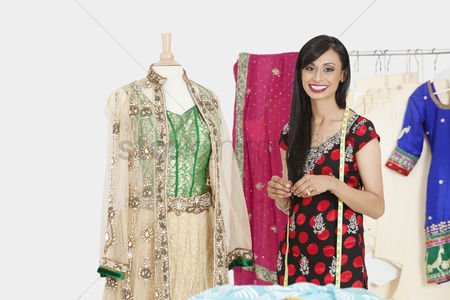 Traditional clothing : Portrait of indian female dressmaker standing by a dummy dressed in traditional wear