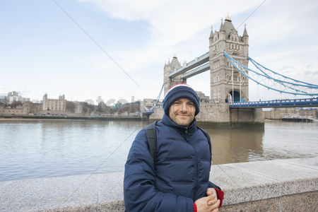England : Portrait of mid adult man in warm clothing standing in front of tower bridge  london  uk