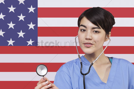 Respect : Portrait of mixed race female surgeon standing over american flag