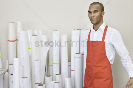 Apron : Portrait of printing press worker standing with paper rolls in background