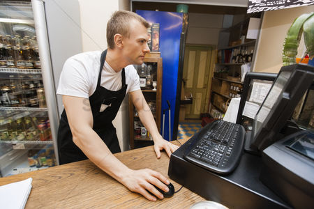 Camera : Portrait of salesman using computer at cash counter in supermarket