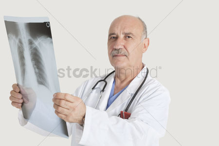 Medical : Portrait of senior doctor holding medical radiograph over gray background