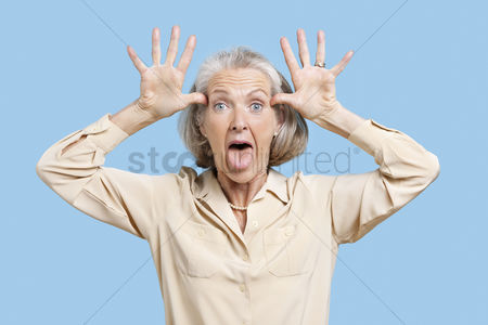 Retirement : Portrait of senior woman making funny faces with hands on head against blue background