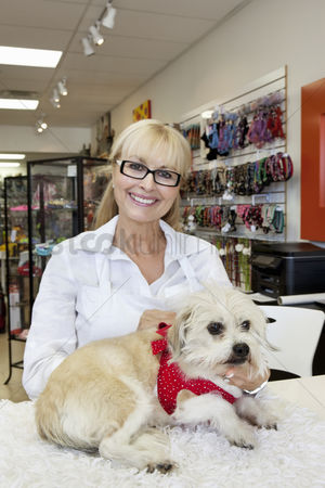 Large group of animals : Portrait of senior woman with dog in pet shop