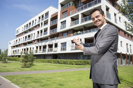 Gesturing : Portrait of smiling real estate agent presenting office building