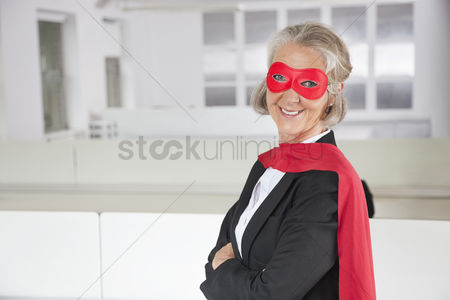 Office worker : Portrait of smiling senior businesswoman in superhero costume in office