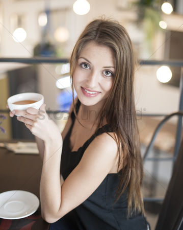 Czech republic : Portrait of smiling young woman having coffee at cafe
