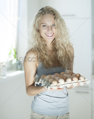 Czech republic : Portrait of woman carrying eggs in kitchen