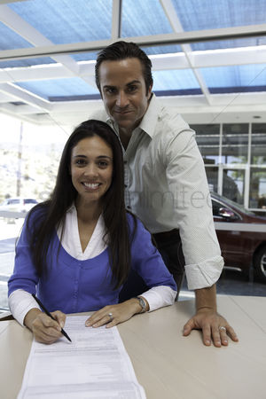 Land : Portrait of woman signing car contract with husband standing behind