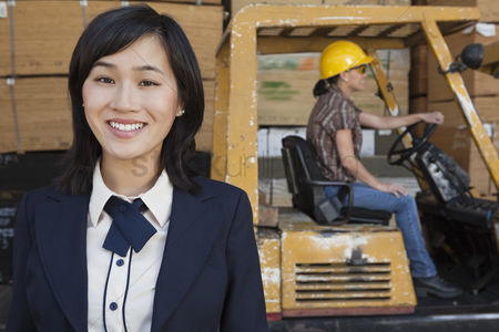 Forklift : Portrait of woman smiling while female industrial worker driving forklift truck in background