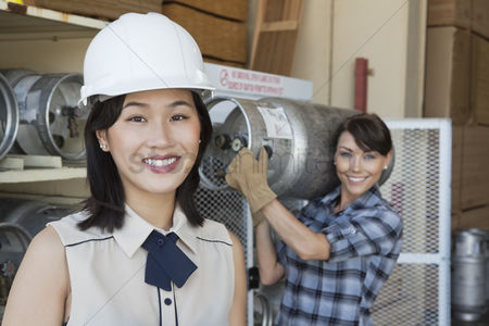 Forklift : Portrait of woman smiling with female industrial worker carrying propane cylinder in background