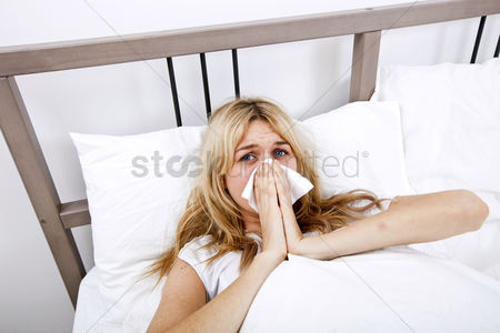 Blowing : Portrait of woman suffering from cold in bed