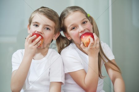 Pre teen : Portrait of young boy and girl in white tshirts eating apples