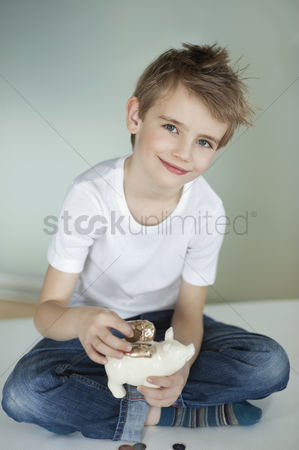 Pocket : Portrait of young boy putting coin in piggy bank