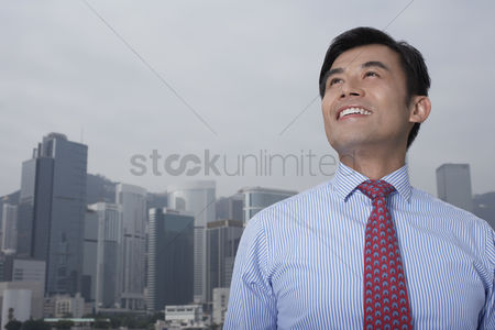 Moody : Portrait of young business man office buildings in background