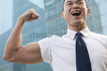 Arm raised : Portrait of young businessman flexing muscle outdoors