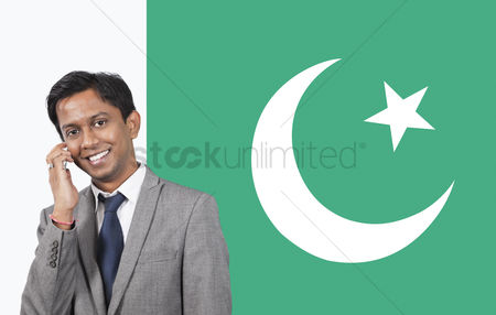 Respect : Portrait of young businessman using cell phone over pakistani flag
