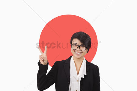 Respect : Portrait of young businesswoman gesturing peace sign over japanese flag