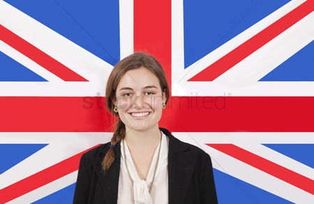 Respect : Portrait of young businesswoman smiling over british flag