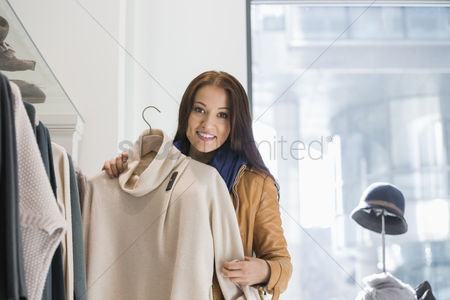Jacket : Portrait of young woman choosing sweater in store