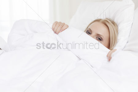 Shyness : Portrait of young woman hiding under bedsheet
