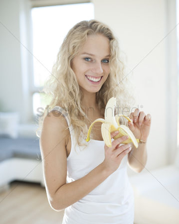 Czech republic : Portrait of young woman peeling banana in house