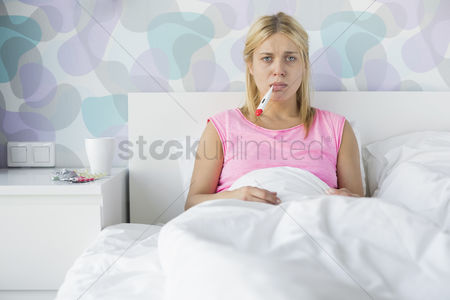 Medication : Portrait of young woman taking temperature with thermometer