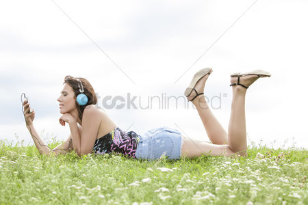 Grass background : Profile shot of woman listening to music through cell phone using headphones while lying on grass against sky