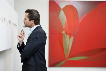 Interior background : Profile view of a young man in a art art gallery
