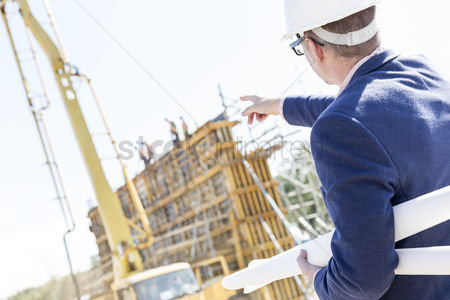 Supervisor : Rear view of architect holding blueprints while pointing at construction site