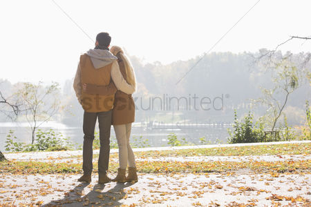 Women : Rear view of couple looking at lake in park during autumn