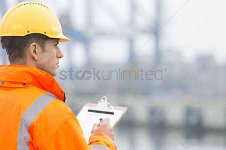 Leadership : Rear view of mid adult man writing on clipboard in shipping yard