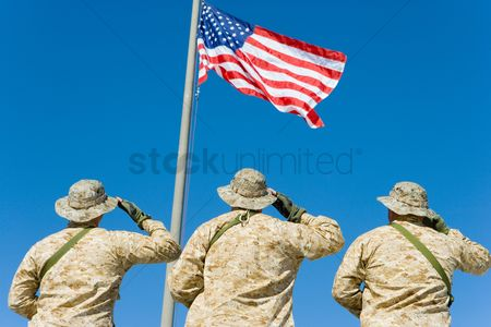 Respect : Rear view of  three u s military personnel saluting the american flag against bright blue sky