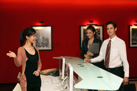 Smiling : Receptionist greeting business people