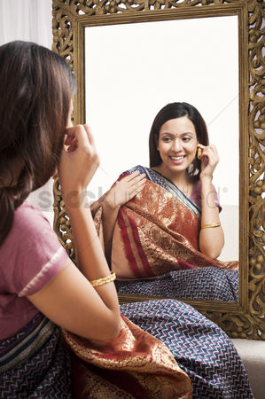 Housewife : Reflection of a woman in mirror trying a sari and earring on herself