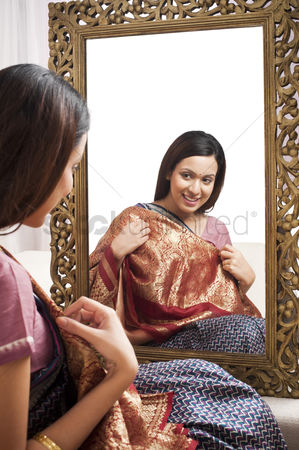 Housewife : Reflection of a woman in mirror trying a sari on herself