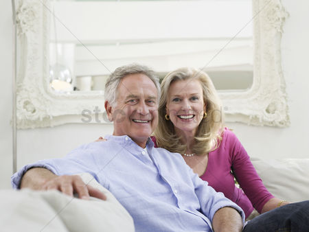 Interior : Relaxed portrait of successful mature couple in white home interior