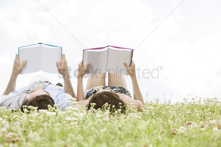 Girlfriend : Relaxed young couple reading books while lying on grass against sky