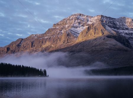 Moody : Rocky mountain fog over lake sunset