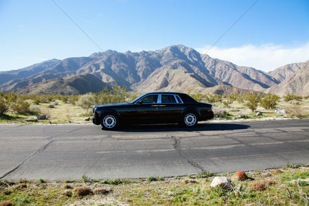 On the road : Rolls royce travelling on country road with mountains in background