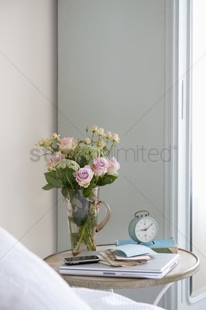 Furniture : Roses in vase on bedside table with books and alarm clock