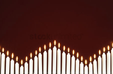 Geometric background : Row of lit candles on black background